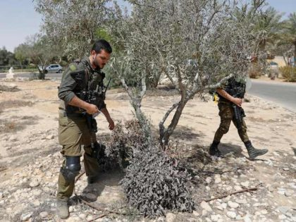 Israeli soldiers search for debris after a missile launched from Syria landed in Ashalim settlement, about 35Km south of Beersheva near the Dimona nuclear power plant in Israel's southern Negev desert, on April 22, 2021. - Multiple defence batteries in Syria were struck by Israeli forces, the military said, after …
