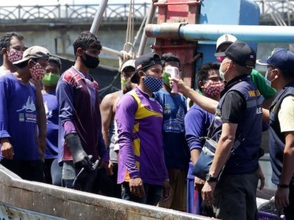 Immigration officers check the temperatures of Myanmar fisherman, as a preventive measure against the spread of the COVID-19 novel coronavirus, at the port in Pattani on April 11, 2020. (Tuwaedaniya Meringing/AFP via Getty Images)