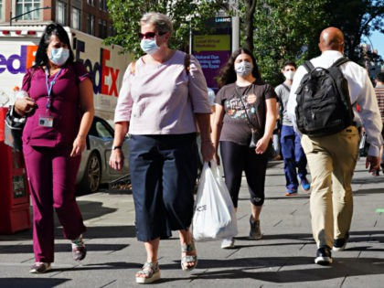 People walk while wearing protective masks as New York City moves into Phase 3 of re-opening following restrictions imposed to curb the coronavirus pandemic on July 14, 2020. Phase 3 permits the reopening of nail and tanning salons, tattoo parlors, spas and massages, dog runs and numerous other outdoor activities. …