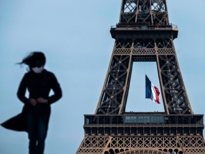 TOPSHOT - A woman wearing a face mask walks as a French national flag flies on the Eiffel Tower in background in Paris on May 11, 2020 on the first day of France's easing of lockdown measures in place for 55 days to curb the spread of the COVID-19 pandemic, …