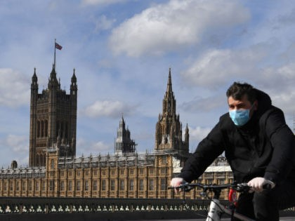 A man wearing a protective face mask cycles across Westminster Bridge, with the Houses of Parliament behind in central London on March 21, 2020, a day after the British government said it would help cover the wages of people hit by the coronavirus outbreak as it tightened restrictions to curb …