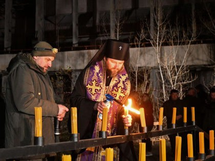 An orthodox priest lights candles on the central square of the ghost town of Pripyat near the Chernobyl Nuclear Power Plant early on April 26, 2021, to commemorate the 35th anniversary of the Chernobyl nuclear disaster. (Photo by Genya SAVILOV / AFP) (Photo by GENYA SAVILOV/AFP via Getty Images)