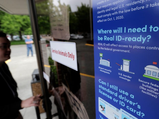 """A customer opens the door of a Washington state Dept. of Licensing office in Lacey, Wash., Friday, June 22, 2018 next to a sign providing information about the requirements of Real ID. Some Washington licenses and identification cards will soon be marked with the words """"federal limits apply"""" as the …"""
