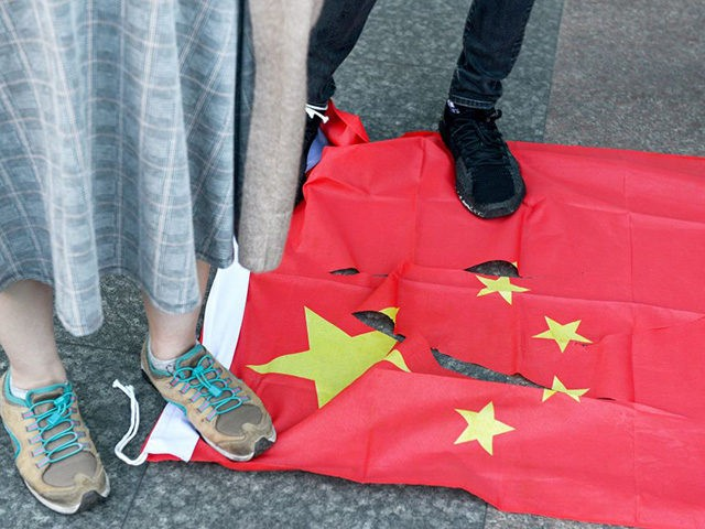 People stand on a torn Chinese national flag during a march in support of Save12, the campaign to save twelve Hong Kong pro-democracy activists who on August 23 were caught by mainland Chinese authorities trying to flee Hong Kong to Taiwan by boat, in central Taipei on October 25, 2020. …