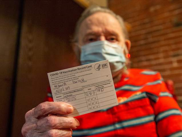 Gerald McDavitt, 81, a Veteran of the United States Army Corps of Engineers, holds his CDC vaccine card after being inoculated with the Johnson & Johnson Covid-19 Janssen Vaccine at his home in Boston, Massachusetts on March 4, 2021. - McDavitt has decided to get the vaccine because his partner …