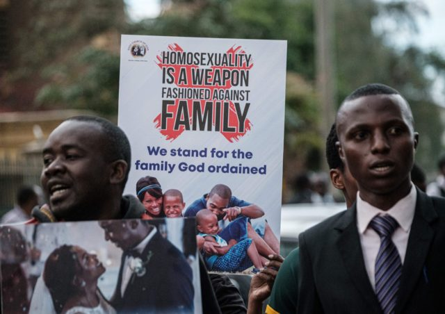 Christian members of the Sozo church of God hold anti-LGBTQ signs and sing against homosexuality after a verdict on scrapping laws criminalising homosexuality in front of the Milimani high court in Nairobi, Kenya, on May 24, 2019. - Kenya's high court, in a much-awaited verdict, refused to scrap laws criminalising …