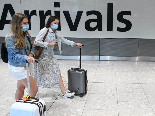 Passengers wearing a face mask or covering due to the COVID-19 pandemic, arrive at Heathrow airport, west London, on July 10, 2020. - The British government on Friday revealed the first exemptions from its coronavirus quarantine, with arrivals from Germany, France, Spain and Italy no longer required to self-isolate from …