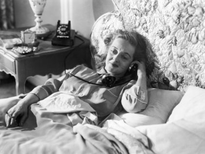 American actress Bette Davis (1908 - 1989) holds a telephone receiver whilst smoking a cigarette in bed in a still from the film 'All About Eve', directed by Joseph L. Mankiewicz, 1950. (Photo by 20th Century Fox/Archive Photos/Getty Images)