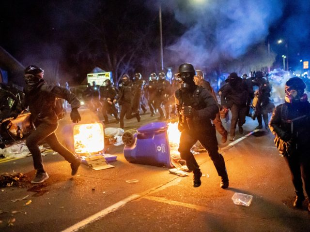 PORTLAND, OR - APRIL 12: Portland police officers chase demonstrators after a riot was declared during a protest against the killing of Daunte Wright on April 12, 2021 in Portland, Oregon. Wright, a Black man whose car was stopped in Brooklyn Center, Minnesota on Sunday reportedly for an expired registration, …