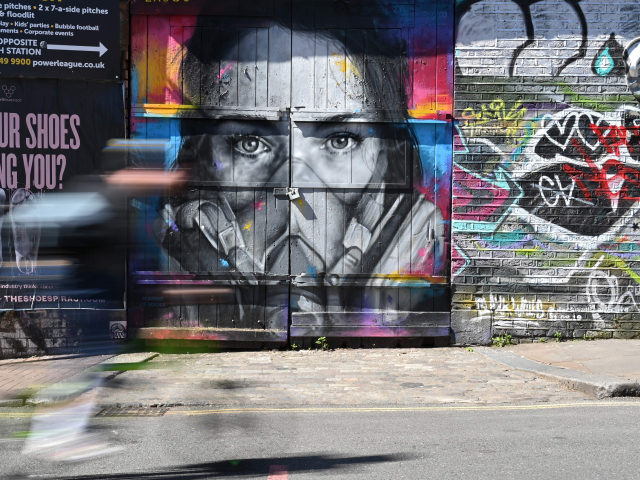 TOPSHOT - A cyclist passes a piece of graffiti of artist BK Foxx wearing her graffiti mask created by French street artist Zabou in East London on April 19, 2020, during the novel coronavirus COVID-19 pandemic. - The number of people in Britain who have died in hospital from coronavirus …