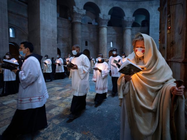 Priests circle the Edicule during Easter Sunday mass led by the Latin Patriarch at the Church of the Holy Sepulchre where Jesus Christ is believed to be buried, in the Old City of Jerusalem, Sunday, April. 4, 2021. (AP Photo/Oded Balilty)