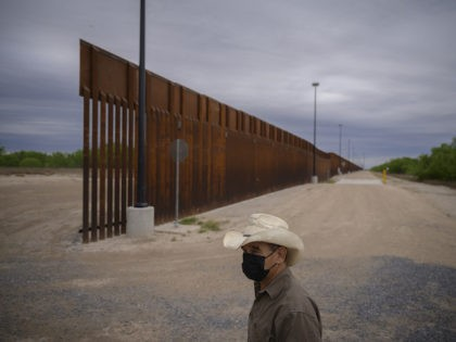 In a photo taken on March 28, 2021 ranch owner Tony Sandoval (67) stands before a portion of the unfinished border wall that former US president Donald Trump tried to build, near the southern Texas border city of Roma. - The 11,000 inhabitants of the Texas border town Roma have …