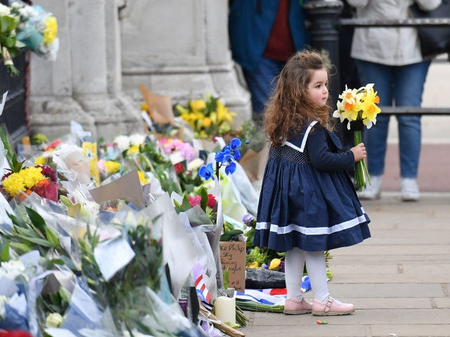 A young child holds a floral tribute as well-wishers take photographs at the gates of Buckingham Palace in central London on April 9, 2021 after the announcement of the death of Britain's Prince Philip, Duke of Edinburgh. - Queen Elizabeth II's husband Prince Philip, who recently spent more than a …