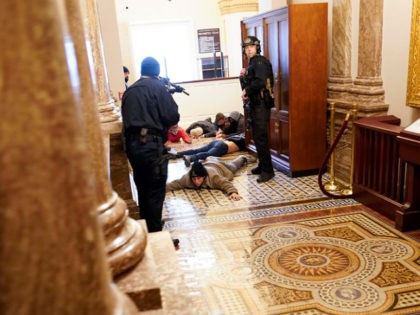 FILE - In this Jan. 6, 2021, file photo U.S. Capitol Police hold insurrectionists loyal to President Donald Trump at gun-point near the House Chamber inside the U.S. Capitol in Washington. A month ago, the U.S. Capitol was besieged by Trump supporters angry about the former president's loss. While lawmakers …