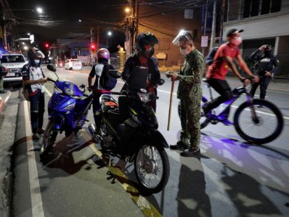Police inspect motorcycle riders at a checkpoint as curfew is imposed to prevent the spread of the coronavirus in metro Manila, Philippines a year after the country imposed a lockdown on Monday, March 15, 2021. The Department of Health has been reporting a surge in infections for more than a …