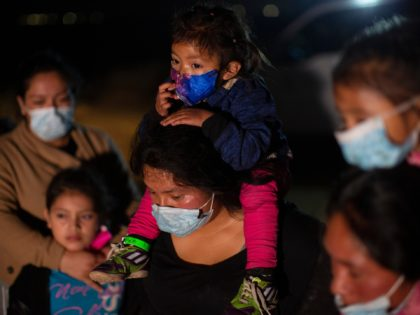 Migrant families coming from Guatemala, wait at a U.S. Border Patrol intake site after they were smuggled on an inflatable raft across the Rio Grande river in Roma, Texas, Wednesday, March 24, 2021. The Biden administration says that it's working to address the increase in migrants coming to the border. …