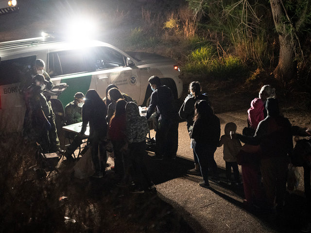 ROMA, TX - APRIL 22: Asylum-seeking migrants' families wait to be transported by the U.S. Border Patrol after crossing the Rio Grande river into the United States from Mexico on April 22, 2021 in Roma, Texas. A surge of mostly Central American immigrants crossing into the United States, including record …