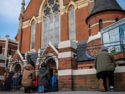 LONDON, ENGLAND - APRIL 04: Christians kneel outside during an Easter Sunday service due to lack of space indoors because of covid-19 social distancing guidelines at Christ the King church on April 4, 2021 in the Balham area of London, England. The church had its Good Friday service interrupted by …