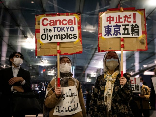 TOKYO, JAPAN - MARCH 25: Demonstrators protest against the Tokyo Olympics outside the building of the Tokyo Organising Committee of the Olympic and Paralympic Games on March 25, 2021 in Tokyo, Japan. Japan's nation-wide torch relay for the postponed Tokyo 2020 Olympics started on Thursday in Fukushima ahead of the …