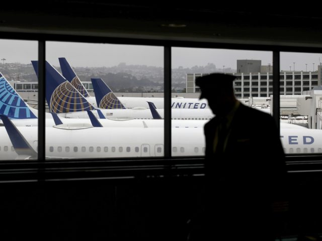 SAN FRANCISCO, CALIFORNIA - APRIL 12: A pilot walks by United Airlines planes as they sit parked at gates at San Francisco International Airport on April 12, 2020 in San Francisco, California. San Francisco International Airport has a seen a huge decline in daily flights since the coronavirus shelter in …