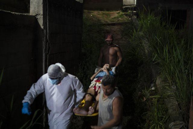 Mobile Emergency Care Service (SAMU) worker Sergio Ricardo, left, and two neighbors, carry an elderly COVID-19 patient to an ambulance in Duque de Caxias, Rio de Janeiro state, Brazil, Wednesday, April 7, 2021. (AP Photo/Felipe Dana)