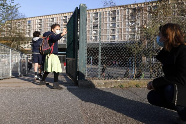 In this Thursday, April 1, 2021 file photo, Emma Woodroof waves goodbye to her mother Julie as she enters her school in Strasbourg, eastern France. Children, parents and teachers are battling with connection problems across France after an abrupt nationwide switch to online learning saturated networks and embarrassed the government. …
