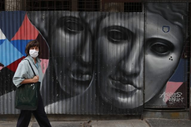 A woman wearing a face mask to protect from the spread of coronavirus, stands in front of a graffiti by the Greek artist Achilles in Athens, Tuesday, April 6, 2021. Lockdown measures have been in force since early November but an ongoing surge in COVID-19 infections remains high as the …