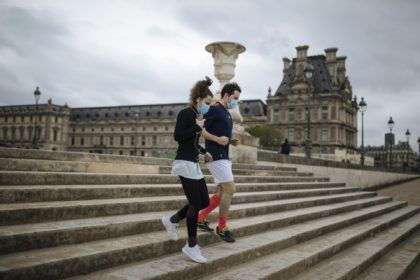 "A masked couple run down the steps of the Tuileries Garden, in Paris, Saturday, April 10, 2021. French President Emmanuel Macron acknowledged Friday that the U.S. ""won the bet"" on coronavirus vaccines by investing massively and moving fast with experimental treatments, and urged his compatriots to join a ""national war …"