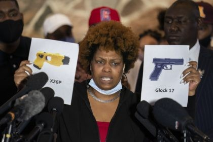 Naisha Wright, aunt of the deceased Daunte Wright, holds up images depicting X26P Taser and a Glock 17 handgun during a news conference at New Salem Missionary Baptist Church, Thursday, April 15, 2021, in Minneapolis. (AP Photo/John Minchillo)