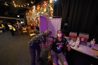 Allison Richter receives the Moderna COVID-19 vaccine from volunteer RN Maggie Baker, during a vaccine event hosted by Nola Ready, where people received a free drink at the bar if they received a COVID-19 vaccine, at The Howling Wolf, a music venue and bar, in New Orleans, Tuesday, April 13, …