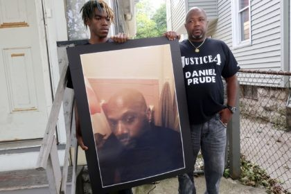 FILE — In this Sept. 3, 2020 file photo, Joe Prude, brother of Daniel Prude, right, and his son Armin, stand with a picture of Daniel Prude in Rochester, N.Y. Newly released transcripts show that a grand jury investigating the police suffocation death of Daniel Prude last year in Rochester, …