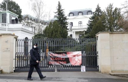 A policeman walks by a poster attached by protesters to a gate of the Russian embassy in Prague, Czech Republic, Friday, April 16, 2021. Czech Republic is expelling 18 diplomats identified as spies over a 2014 ammunition depot explosion. On Saturday, April 17, 2021, Prime Minister Andrej Babis said the …