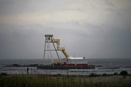 A man who did not want to be identified surveys his company's barge that ran aground during a storm on Tuesday, that also capsized a lift boat, killing one with 12 others still missing in the Gulf of Mexico, in Grand Isle, La., Thursday, April 15, 2021. (AP Photo/Gerald Herbert)
