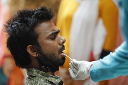 A health worker takes a swab sample to test for COVID-19 in Prayagraj, India, Saturday, April 17, 2021. The global death toll from the coronavirus topped a staggering 3 million people Saturday amid repeated setbacks in the worldwide vaccination campaign and a deepening crisis in places such as Brazil, India …