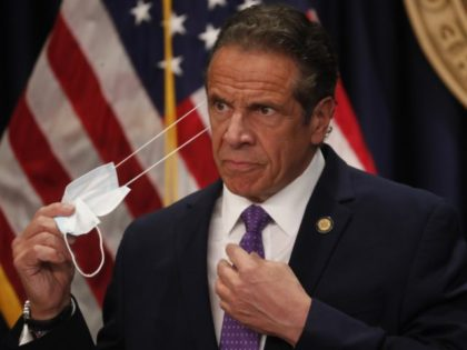 Gov. Andrew Cuomo takes off his face mask before a news conference in New York on Monday, April 19, 2021. Cuomo is allowing more people to go inside museums, movie theaters and indoor big sports arenas as the latest data suggests the state's massive vaccination campaign is curbing COVID-19 infection …