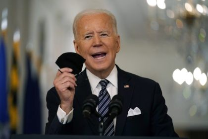 In this March 11, 2021, file photo, President Joe Biden holds up his face mask as he speaks about the COVID-19 pandemic during a prime-time address from the East Room of the White House in Washington. The U.S. is meeting President Joe Biden's latest vaccine goal of administering 200 million …