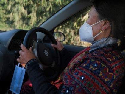 An extra face mask hangs by the steering wheel of nurse Shimray Wungreichon, 43, as she drives home from a day at work at the District Hospital in Ukhrul, in the northeastern Indian state of Manipur, Friday, Jan. 15, 2021. For the first three months, she couldn't hug her three …