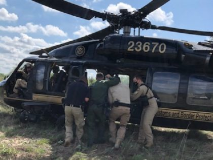 A CBP AMO agent and Border Patrol agents load a distressed migrant woman into a Black Hawk helicopter in Brooks County, Texas. (Photo: CBP Air and Marine Operations/McAllen Air Branch)