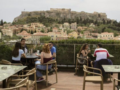 People sit in on a cafe terrace, in the Monastiraki district of Athens, with the ancient Acropolis hill in the background, Monday, May 3, 2021. Cafes and restaurants have reopened in Greece for sit-down service for the first time in nearly six months, as the country began easing coronavirus-related restrictions …