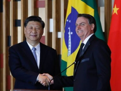 Chinese President Xi Jinping (L) and Brazilian President Jair Bolsonaro shake hands during a press statement after their bilateral meeting at Itamaraty Palace in Brasilia, Brazil, on November 13, 2019. - Brazil's President Jair Bolsonaro walked a diplomatic tightrope, as he seeks to boost ties with Beijing and avoid upsetting …