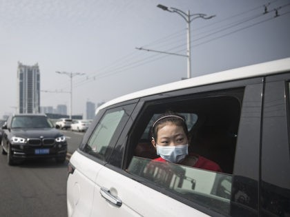 A girl sit in car while traffic stops during a silent tribute to martyrs who died in the fight against the novel coronavirus disease (COVID-19) outbreak and compatriots who died of the disease on April 4,2020 in Wuhan, Hubei Province, China.will lift the lockdown on April 8, local media reported. …