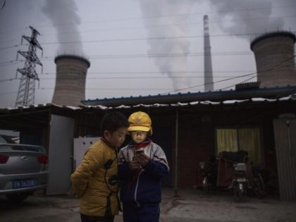 Chinese boys look at their smartphone in front of their house next to a coal fired power plant on November 27, 2015 on the outskirts of Beijing, China. China's government has set 2030 as a deadline for the country to reach its peak for emissions of carbon dioxide, what scientists …