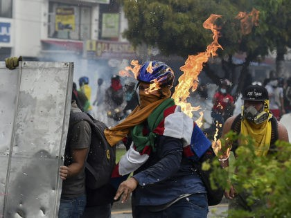 A demonstrator is hit by a Molotov cocktail thrown during clashes with riot police officers during a protest against a proposed government tax reform in Cali, Colombia, on May 3, 2021. - Protesters in Colombia on May 3 called for a new mass rally after 19 people died and more …