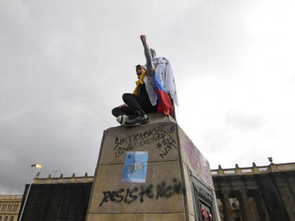 A student raises his fist from the top of a statue of liberator Simon Bolivar during the second day of protests against a tax reform bill launched by Colombian President Ivan Duque, in Bogota, on April 29, 2021. - Workers' unions, teachers, civil organizations, indigenous people and other sectors reject …