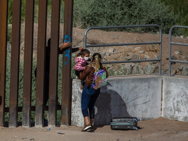 YUMA, AZ - May 13, 2021: A familiy of asylum seekers from Cuba jump the wall to turn themselves to the US Border Patrol Agents on May 12, 2021 in Yuma, Arizona. Migrants Continue To Cross Southern Border As Biden Administration Grapples With Surge. (Photo by Apu Gomes/Getty Images)