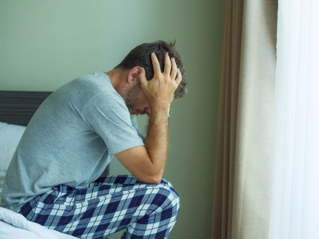 dramatic portrait of attractive scared and depressed 40s man on bed in pajamas feeling worried suffering anxiety and depression problem during virus quarantine home lockdown - stock photo dramatic portrait of attractive scared and depressed 40s man on bed in pajamas feeling worried suffering anxiety and depression problem during virus …