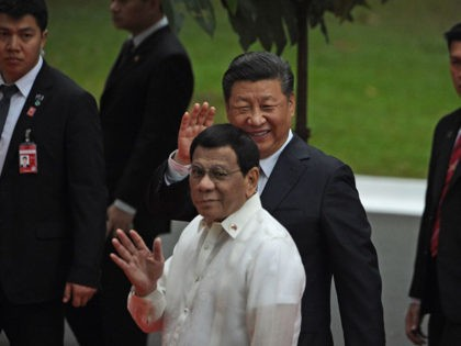 China's President Xi Jinping (back C) and Philippines' President Rodrigo Duterte wave to members of the media after inspecting the honour guard during a welcoming ceremony at the Malacanang palace grounds in Manila on November 20, 2018. - Chinese President Xi Jinping called his visit on November 20 to long-time …