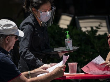 A waiter at Raku, an Asian restaurant in Bethesda, provides hand sanitizer and wears a protective face mask as they work amid the coronavirus pandemic on June 12, 2020 in Bethesda, Maryland. Many streets are closed to vehicles in downtown Bethesda as Montgomery County continues its phase one easing of …