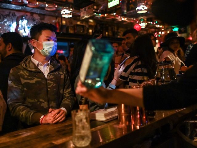 A man wearing a face mask as a preventive measure against the spread of the COVID-19 novel coronavirus, is seen while people dance in a bar in Shanghai on April 26, 2020. - China's economy shrank for the first time in decades last quarter as the coronavirus paralysed the country, …