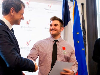 American Alek Skarlatos (C) shakes hands with Emmanuel Lebrun-Damiens, French Consul General in San Francisco, after being given his naturalization certificate during a ceremony at the Alliance Francaise in Sacramento, California, January 31, 2019. - American citizens Anthony Sadler, Alek Skarlatos and Spencer Stone received honorary French citizenship after foiling …